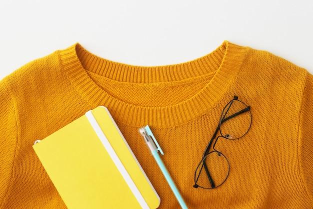 Un collier d'un pull jaune vif avec un carnet, un stylo et des lunettes