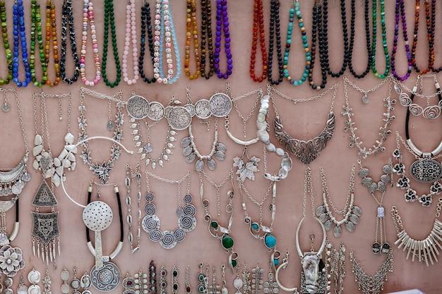 Des colliers en métal et colorés sont accrochés au mur monochrome du marché décorations de différentes