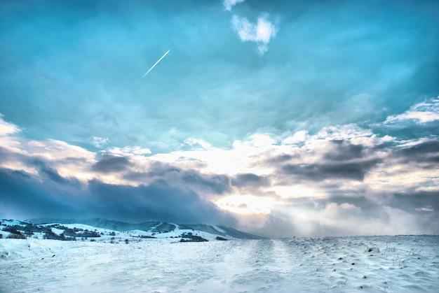 Collines d'hiver couvertes de neige contre le coucher du soleil