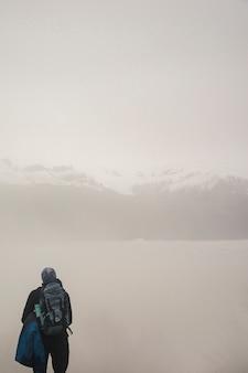 Collines des montagnes brumeuses et randonneur actif avec sac à dos au premier plan