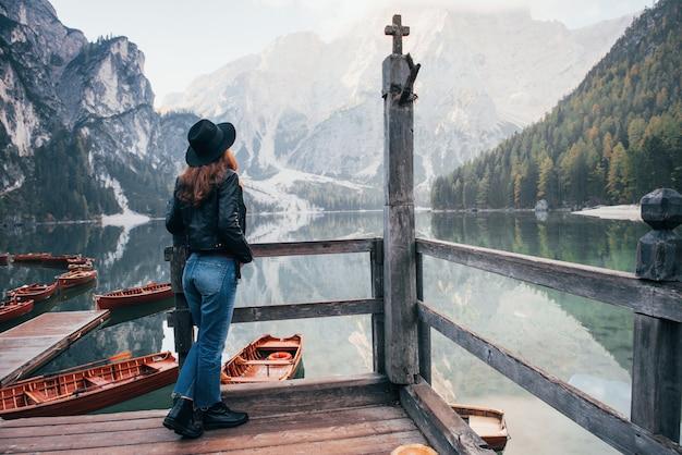 Collines et vallées. femme, dans, chapeau noir, apprécier, majestueux, paysage montagne, près, les, lac, à, bateaux