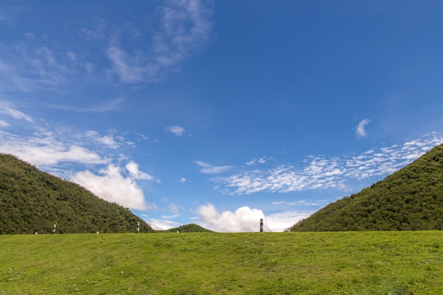 Collines verdoyantes et clôture herbe luxuriante, ciel bleu avec des nuages blancs