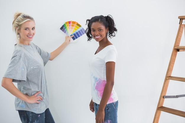 Colocataires choisir une couleur pour un mur blanc et sourire à la caméra