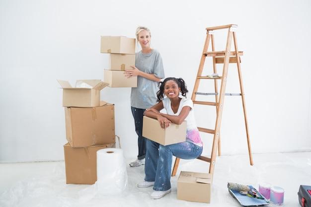 Colocataires souriants portant des boîtes de déménagement en carton