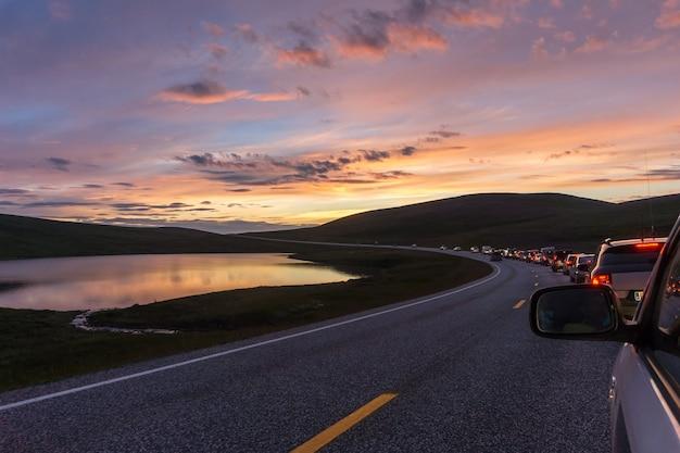 Une colonne de voitures sur une route sinueuse sur fond de montagnes et de mer au coucher du soleil