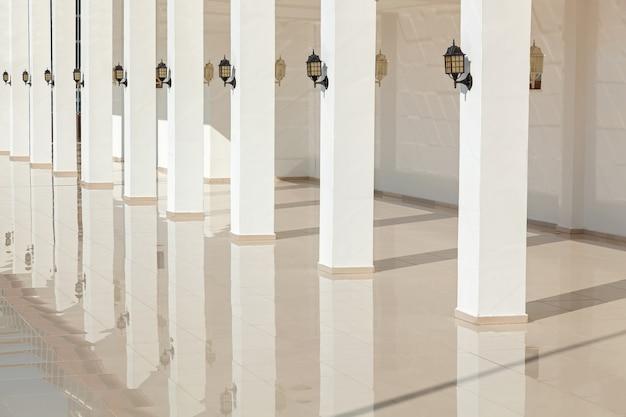 Les colonnes du bâtiment se reflètent sur un sol lisse