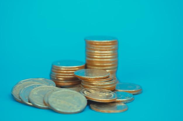 Colonnes de pièces de monnaie, piles de pièces de monnaie sur fond bleu, concept commercial et financier.