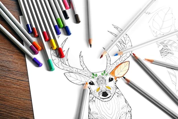 Coloration du cerf avec des crayons sur la table