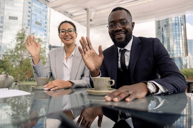 Cols blancs asiatiques et africains agitant la main à leurs collègues lors d'une réunion en ligne