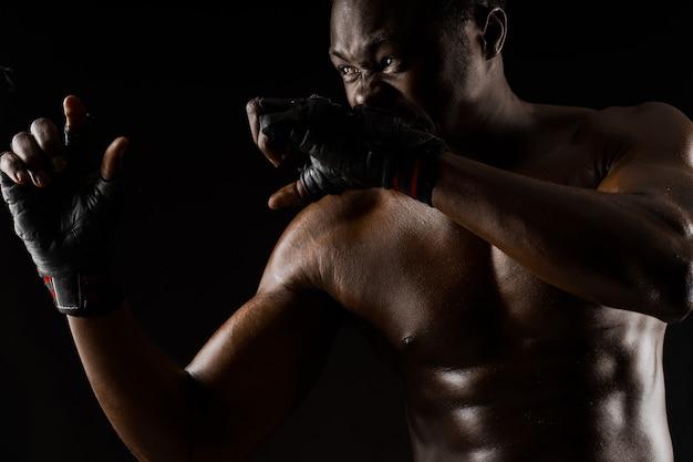 Combattant africain athlétique sur fond noir. un homme déshabillé à la peau foncée montre un combat. annonce pour club de sport et salle de gym. boxe et karaté professionnels.