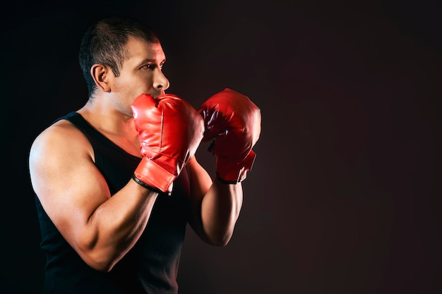 Le combattant boxe et s'entraîne avec des gants de boxe et porte une chemise