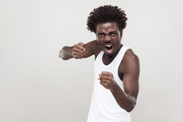 Combattant dangereux. homme afro prêt à se battre. prise de vue en studio. fond gris