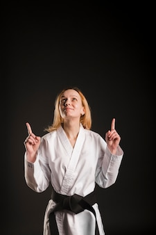 Combattant féminin pointant vers le haut plan moyen