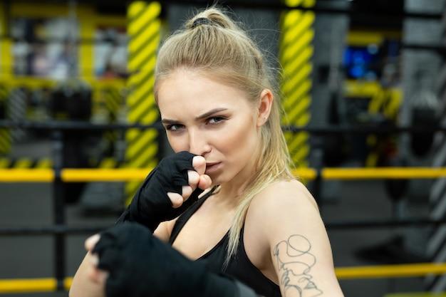 Combattant fille athlétique s'entraîne dans des bandages de boxe s