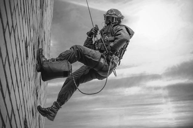 Un combattant des forces spéciales descend d'un gratte-ciel pour prendre d'assaut l'appartement. swat, police, concept de contre-terrorisme.