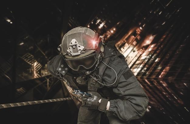 Un combattant des forces spéciales descend d'un gratte-ciel pour prendre d'assaut l'appartement
