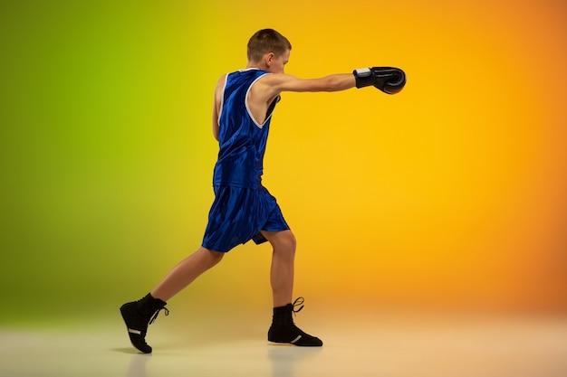 Combattant. formation de boxeur professionnel adolescent en action, mouvement isolé sur fond dégradé à la lumière du néon. coup de pied, boxe. concept de sport, mouvement, énergie et mode de vie sain et dynamique.