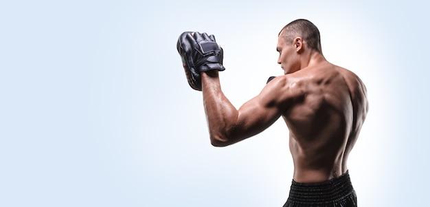 Combattant musclé posant avec des pattes de boxe. concept d'arts martiaux mixtes.
