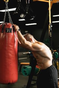 Combattant musculaire fatigué pendant son entraînement avec un sac de boxe