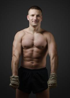 Combattant musculaire muay thai combat l'échauffement avant une séance d'entraînement ou aux mains d'une corde de chanvre