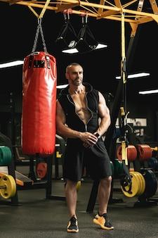 Combattant musculaire pendant son entraînement avec un sac de boxe dans la salle de sport