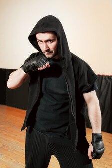 Combattant de rue agressif en tissu de sport noir