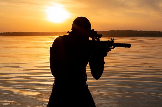 Le combattant d'une unité spéciale quitte l'eau et se prépare pour le début de l'opération. technique mixte. le concept d'instabilité dans le monde, hostilités, crise. russie vs usa