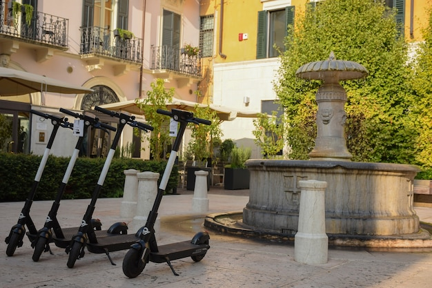 Combien de scooters électriques sont alignés près d'une fontaine dans la vieille ville