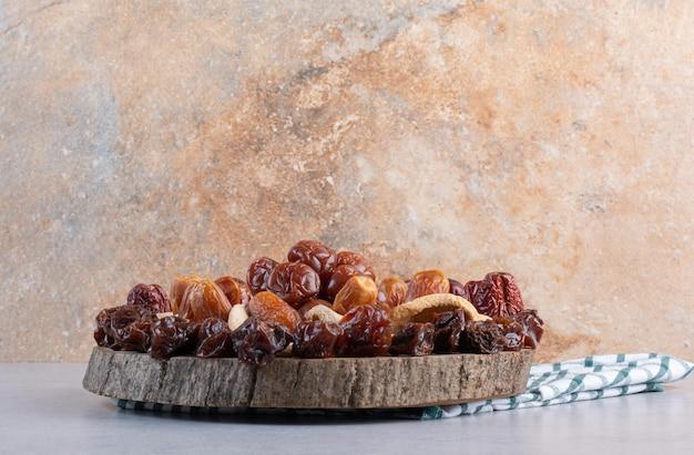 Combinaison de fruits secs sur un plateau sur fond de béton.