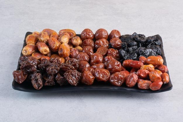 Combinaison de fruits secs sur un plateau sur une surface en béton.