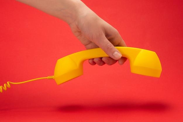 Combiné jaune dans la main de la femme.