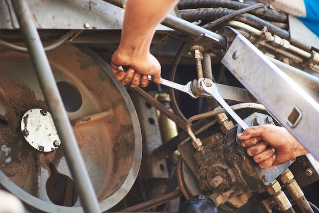 Combinez le service de la machine, le mécanicien réparant le moteur à l'extérieur.