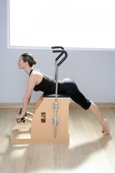 Combo wunda chaise de pilates avec femme faisant du yoga fitness