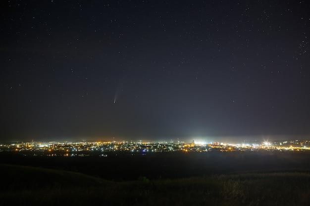 Comète lumineuse c / 2020 f3 (neowise) dans le ciel étoilé. objet de l'espace lointain au-dessus d'une ville avec un éclairage public lumineux.