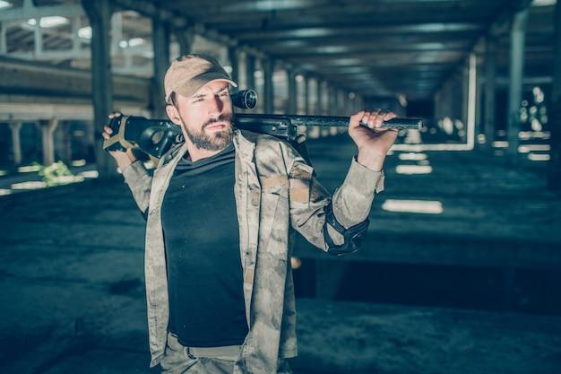 Le commandant calme et paisible est debout et pose. il regarde de côté. le gars a aussi un fusil dans les mains mais reste derrière le cou. il se tient dans un hangar par une journée ensoleillée.