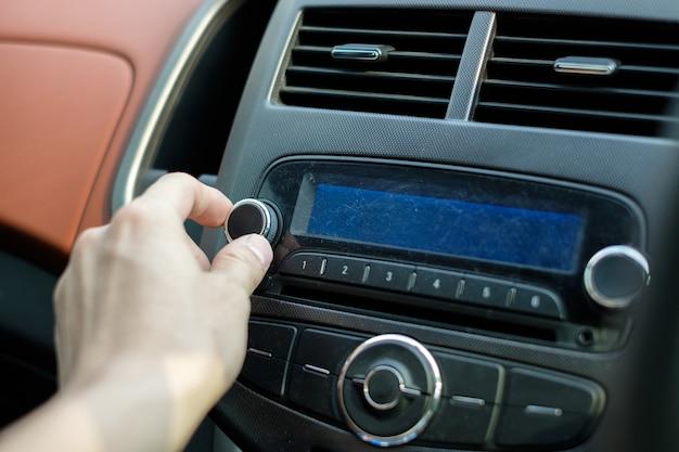 Commande audio de voiture de bouton de cadran de réglage de main d'homme
