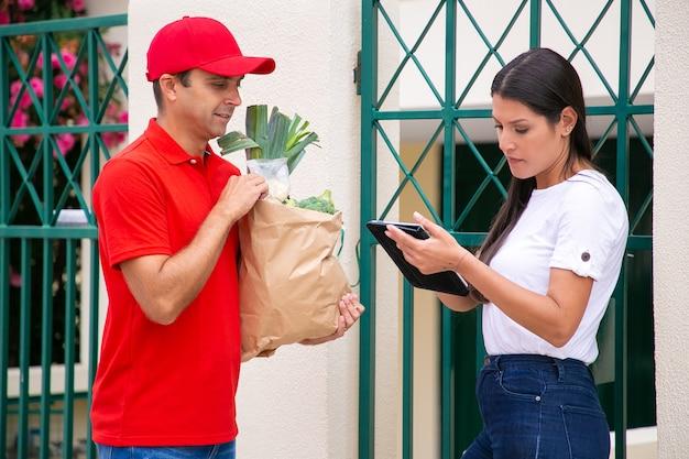 Commande de contrôle client femelle sur tablette et debout près de courrier. livreur tenant un sac en papier avec des légumes et livrant la commande à pied. service de livraison de nourriture et concept d'achat en ligne
