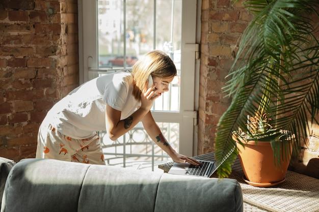 Commande en cours de traitement. femme caucasienne, pigiste pendant le travail au bureau à domicile pendant la quarantaine. jeune femme d'affaires à la maison, auto isolée. utilisation de gadgets. travail à distance, prévention de la propagation du coronavirus.
