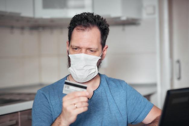 Commande de nourriture et de médicaments dans une boutique en ligne pendant la quarantaine et l'épidémie, portrait d'un homme dans un masque médical