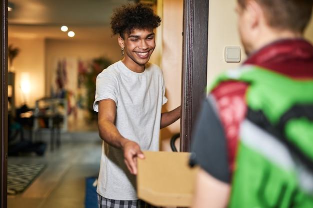 Commander de la nourriture en ligne un jeune homme joyeux qui a l'air heureux tout en rencontrant un coursier avec des dépenses en boîte à pizza