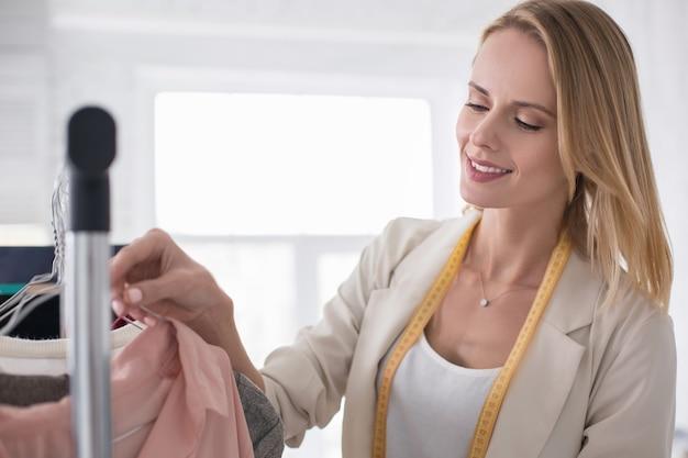 Commandez dans tout. joyeuse femme d'affaires gay gérant le vêtement sur le stand en souriant