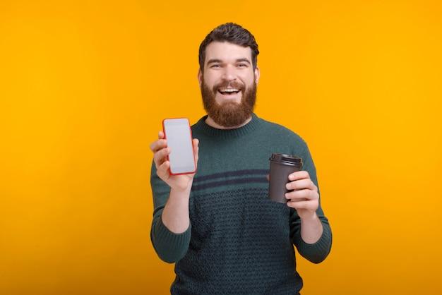 Commandez votre café en ligne. l'homme excité tient dans ses mains pour aller tasse de papier café et un téléphone à écran vide sur l'espace jaune.