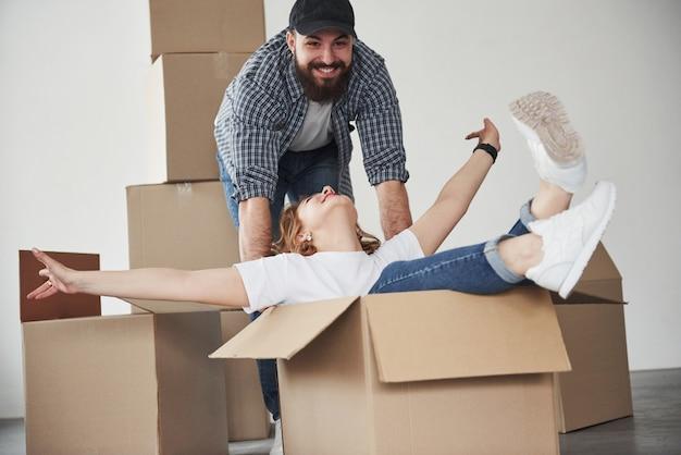 Comme des enfants à nouveau. heureux couple ensemble dans leur nouvelle maison. conception du déménagement