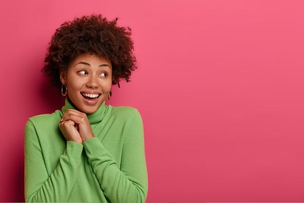 Comme c'est gentil! une jolie femme positive a les cheveux afro touffus, se détourne, admire quelque chose de très agréable, garde les mains jointes, sourit largement, a une peau sombre et saine