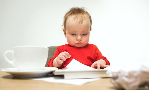 Comme je suis fatigué. enfant bébé fille assise avec clavier d'ordinateur moderne ou ordinateur portable en studio blanc