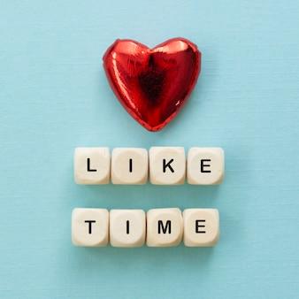 Comme des mots de temps, faits de lettres en bois avec coeur rouge sur fond bleu