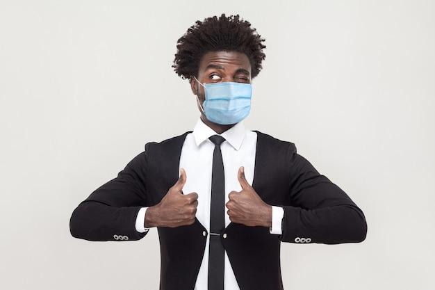 Comme. portrait d'un jeune travailleur hamdsome satisfait et drôle portant un costume noir avec un masque médical chirurgical debout, les pouces vers le haut et en détournant les yeux. tourné en studio intérieur isolé sur fond gris.