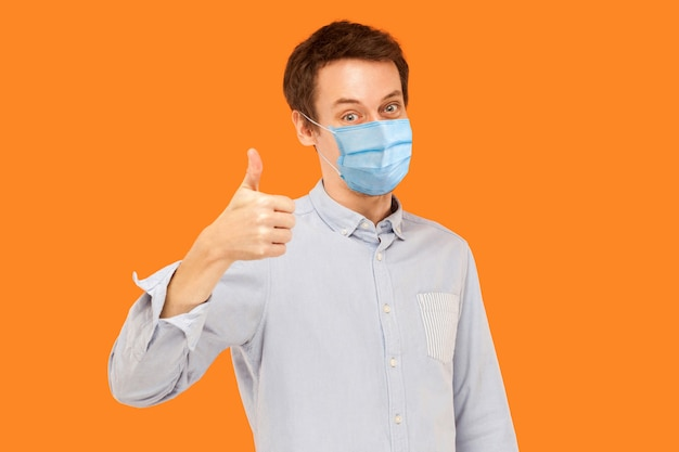 Comme. portrait d'un jeune travailleur satisfait avec un masque médical chirurgical debout les pouces vers le haut et regardant la caméra en souriant. tourné en studio intérieur isolé sur fond orange.