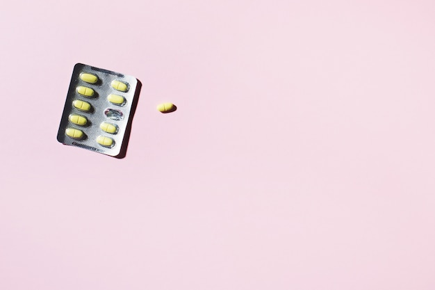 A commencé l'assiette de pilules avec des ombres de gelée sur un fond jaune.