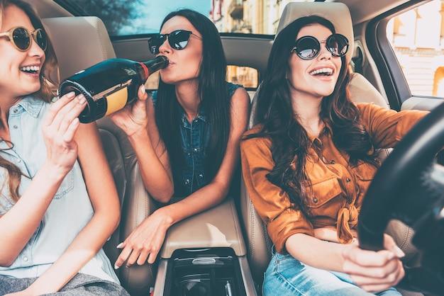 Commencer un nouveau voyage avec du champagne. trois belles jeunes femmes gaies